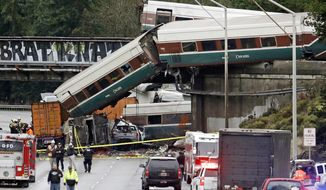 FILE - In this Dec. 18, 2017, file photo, cars from an Amtrak train lay spilled onto Interstate 5 alongside smashed vehicles as some train cars remain on the tracks above in DuPont, Wash. Federal safety investigators are expected to present their findings Tuesday, May 21, 2019, on the Amtrak train derailment south of Seattle that killed three people and injured dozens. (AP Photo/Elaine Thompson, File)