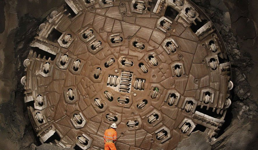 "In this Oct. 15, 2010, file photo, a miner stands in front of the drill machine ""Sissi"" after it broke through the rock at the final section Faido-Sedrun, at the construction site of the NEAT Gotthard Base Tunnel. With a length of 57 km (35 miles) crossing the Alps, the world's longest train tunnel should become operational at the end of 2017.       (AP Photo/Christian Hartmann, Pool, File)"
