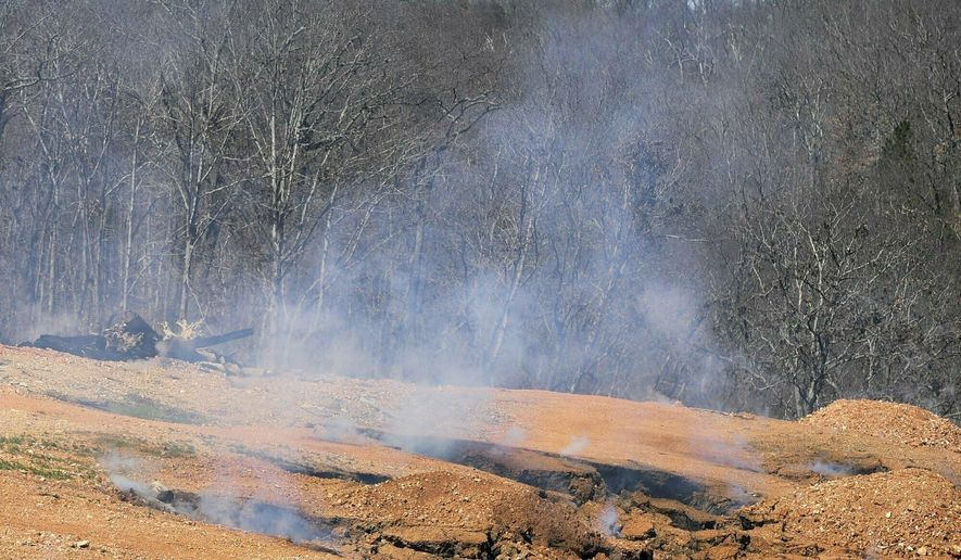 In this Friday, March 15, 2019 photo, smoke rises from an underground fire in Bella Vista, Ark. Residents who live near the underground fire in northwest Arkansas should be prepared for unsafe air conditions while contractors work to extinguish the blaze, the local property association said. (Charlie Kaijo/The Northwest Arkansas Democrat-Gazette via AP)