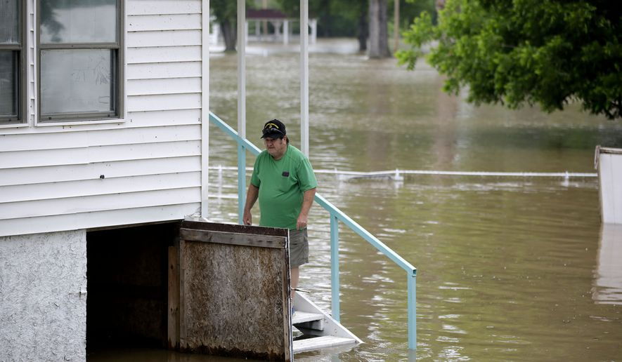 Andy Paul stands on the steps to his home as water from the Arkansas River approaches in Webbers Falls, Okla., Wednesday, May 22, 2019. (Mike Simons/Tulsa World via AP)