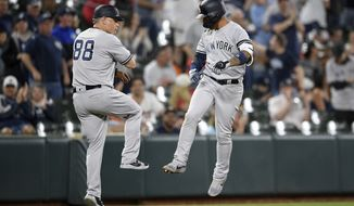 New York Yankees' Gleyber Torres, right, celebrates his home run with third base coach Phil Nevin (88) during the fifth inning of the team's baseball game against the Baltimore Orioles, Wednesday, May 22, 2019, in Baltimore. The Yankees won 7-5. (AP Photo/Nick Wass)