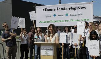 "Emily Cunningham, center, who works as a user experience designer at Amazon.com, speaks during a news conference following Amazon's annual shareholders meeting, Wednesday, May 22, 2019, in Seattle held by the group ""Amazon Employees for Climate Justice."" (AP Photo/Ted S. Warren)"