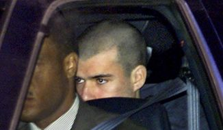 FILE - In this Jan. 24, 2002 file photo,  John Walker Lindh, far right, leaves the Alexandria Detention Center in Alexandria, Va., before dawn, on the way to his first appearance in a nearby federal court. Lindh, the young Californian who became known as the American Taliban after he was captured by U.S. forces in the invasion of Afghanistan in late 2001, is set to go free Thursday, May 23, 2019, after nearly two decades in prison. (AP Photo/J. Scott Applewhite, File)