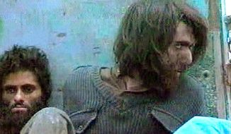 FILE - This file image taken Dec. 1, 2001, from television footage in Mazar-i-Sharif, Afghanistan, shows John Walker Lindh, right, claiming to be an American Taliban volunteer. Lindh, the young Californian who became known as the American Taliban after he was captured by U.S. forces in the invasion of Afghanistan in late 2001, is set to go free Thursday, May 23, 2019, after nearly two decades in prison.   (AP Video, File)