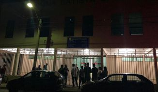 "In this photo released by Agora News, residents stand at the entrance of a Baptist church where a man killed three people after he knifed his girlfriend in her home, in Paracatu, Minas Gerais state, Brazil, Tuesday, May 21, 2019. The gunman was then shot and wounded by military police at the church. Authorities did not provide a motive for the attack, but said the wounded man had been expelled by the church for ""problems of behavior."" (Marco Aurelio Costa/Agora News via AP)"