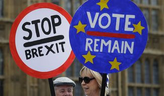 Anti Brexit campaigners hold banners near Parliament in London, Wednesday, May 22, 2019. British Prime Minister Theresa May was under pressure Wednesday to scrap a planned vote on her tattered Brexit blueprint — and to call an end to her embattled premiership — after her attempt at compromise got the thumbs-down from both her own Conservative Party and opposition lawmakers. (AP Photo/Kirsty Wigglesworth)