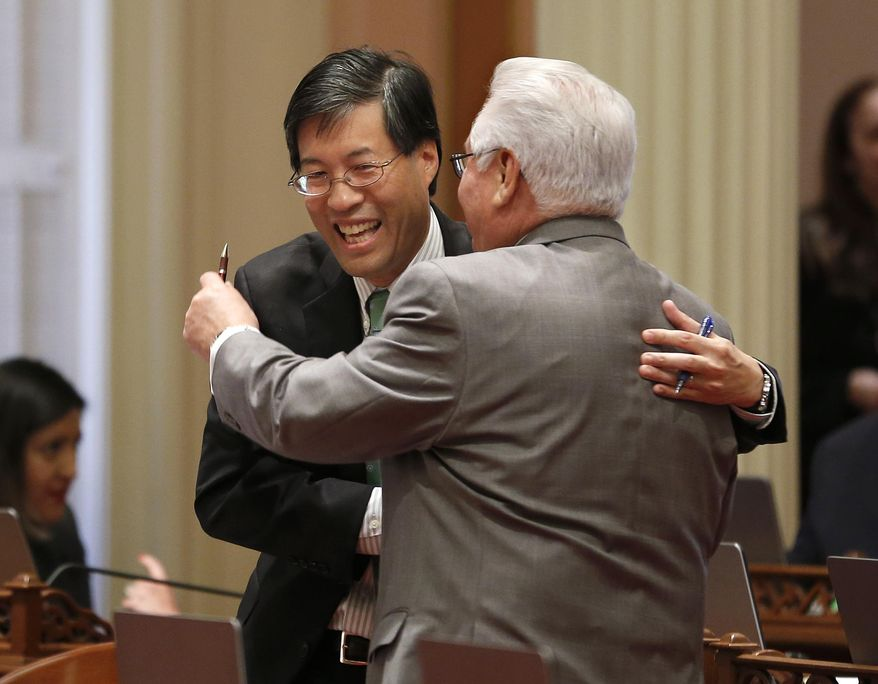 State Sen. Richard Pan, D-Sacramento, left, receives congratulations from Southern California Democratic state Sen. Bob Archuleta, right, after his measure to toughen the rules for vaccination exemptions was approve by the Senate, Wednesday, May 22, 2019, in Sacramento, Calif. The bill, SB276, gives state public health officials instead of local doctors the power to decide which children can skip their shots before attending school. (AP Photo/Rich Pedroncelli)