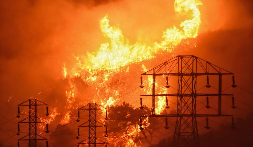 """FILE - In this Dec. 16, 2017, file photo provided by the Santa Barbara County Fire Department, flames burn near power lines in Sycamore Canyon near West Mountain Drive in Montecito, Calif. Pacific Gas & Electric Corp. has received approval to establish a $105 million fund to help survivors of recent California wildfires started by the utility's power lines. A federal judge overseeing PG&E's bankruptcy case approved the utility's """"wildfire assistance program"""" on Wednesday, May 22, 2019. (Mike Eliason/Santa Barbara County Fire Department via AP, File)"""