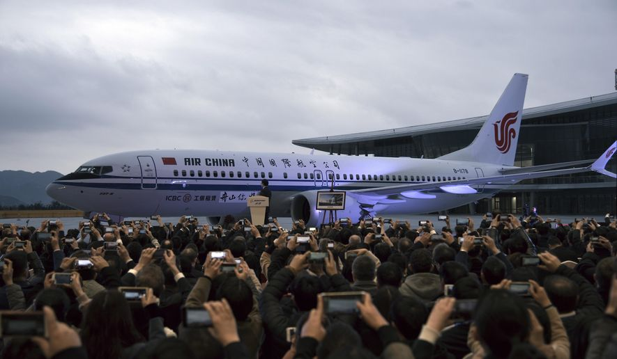 In this Dec. 15, 2018, photo, invited guests take photos of the Boeing 737 Max 8 airplane deliver to Air China during a ceremony at Boeing Zhoushan 737 Completion and Delivery Center in Zhoushan, east China's Zhejiang Province. Air China, one of China's three major state-owned airlines, is joining carriers that want compensation from Boeing Co. for the grounding of its 737 Max jetliner following two fatal crashes. The airline said it wants unspecified compensation for the grounding of its 15 Max aircraft and delays in delivery of new planes. It is the second major Chinese carrier to ask for compensation following China Eastern in April, 2019. (Chinatopix via AP)