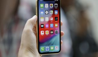 This Sept. 12, 2018, file photo shows an Apple iPhone XR on display at the Steve Jobs Theater after an event to announce new products, in Cupertino, Calif. (AP Photo/Marcio Jose Sanchez, File)