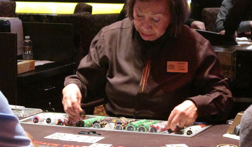 This Feb. 22, 2019 file photo shows a dealer handling chips in a New Jersey casino. Wynn Resorts said Wednesday its Encore Boston Harbor casino will open June 23, making the $2.6 billion casino the first such facility in the Boston, Mass., metropolitan area. (AP Photo/Wayne Parry) **FILE**