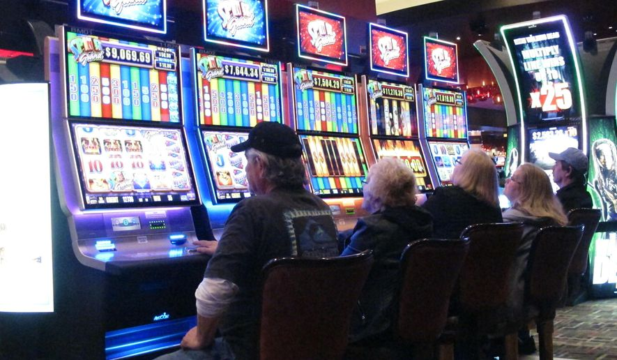 This Feb. 22, 2019 photo shows gamblers playing slot machines in the Golden Nugget casino in Atlantic City N.J. Figures released by New Jersey gambling regulators on May 22, 2019 show that gross operating profit for Atlantic City's nine casinos declined by nearly 30 percent in the first quarter of this year compared to the same period last year, when there were only seven casinos. (AP Photo/Wayne Parry)