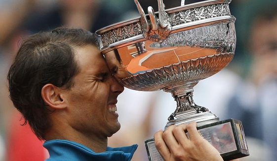 FILE - In this June 10, 2018, file photo, Spain's Rafael Nadal reacts while holding the trophy after defeating Austria's Dominic Thiem in the men's finals of the French Open tennis tournament in Paris. Nadal, a French Open champion yet again a week past his 32nd birthday seems to stay forever young. (AP Photo/Thibault Camus, File)