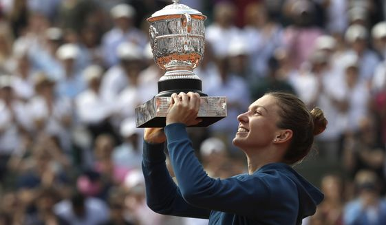 FILE - In this June 9, 2018, file photo, Romania's Simona Halep holds the trophy as she celebrates after defeating against Sloane Stephens, of the United States, 3-6, 6-4, 6-1, in the finals of the French Open tennis tournament at the Roland Garros stadium in Paris, France. (AP Photo/Alessandra Tarantino, File)