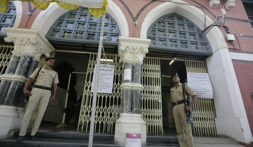 Indian policemen stand guard outside a vote counting center in Ahmadabad, India, Wednesday, May 22, 2019. India's Election Commission has rejected opposition fears of possible tampering of electronic voting machines ahead of Thursday's vote-counting to determine the outcome of the country's mammoth national elections. Authorities on Wednesday tightened security at counting centers where the electronic voting machines have been kept in strong rooms across the country. (AP Photo/Ajit Solanki)