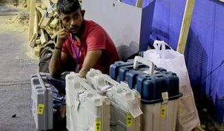 FILE- In this May 18, 2019 file photo, a polling officer sits with Electronic Voting Machines (EVM) at a distribution center on the eve of polls in Kolkata, India. India's Election Commission has rejected opposition fears of possible tampering of electronic voting machines ahead of Thursday's vote-counting to determine the outcome of the country's mammoth national elections. (AP Photo/Bikas Das, file)