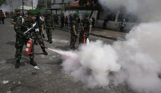 Indonesian soldiers extinguish burning tires during a clash between protesters and the police in Jakarta, Indonesia, Wednesday, May 22, 2019. Supporters of an unsuccessful presidential candidate clashed with security forces in the Indonesian capital on Wednesday, burning vehicles and throwing rocks at police using tear gas and rubber bullets. (AP Photo/Dita Alangkara)
