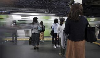 Commuters wait to get on a train at a station Wednesday, May 22, 2019, in Tokyo. A police-developed smartphone app with anti-sex crime alarms has won massive subscriptions as Japanese women try to arm themselves against gropers on packed rush-hour trains. (AP Photo/Eugene Hoshiko)