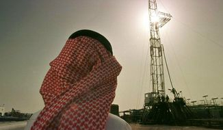 FILE - In this Feb. 26, 1997 file photo, Khaled al-Otaiby, an official of the Saudi oil company Aramco, watches progress at a rig at the al-Howta oil field near Howta, Saudi Arabia.  Saudi Aramco will begin buying liquid natural gas from a U.S. company under a 20 year agreement.  Saudi Aramco said Wednesday, May 22, 2019, it would buy 5 million tons of liquid natural gas per year from Sempra Energy, based in San Diego.(AP Photo/John Moore, File)