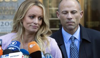 FILE - In this April 16, 2018 file photo, adult film actress Stormy Daniels, left, stands with her lawyer Michael Avenatti as she speaks outside federal court, in New York. Avenatti, the attorney who rocketed to fame through his representation of Daniels in her battles with President Donald Trump, was charged Wednesday, May 22, 2019, with ripping her off. Federal prosecutors in New York City say Avenatti used a doctored document to divert about $300,000 that Daniels was supposed to get from a book deal, then used the money for personal and business expenses.  (AP Photo/Mary Altaffer, File)