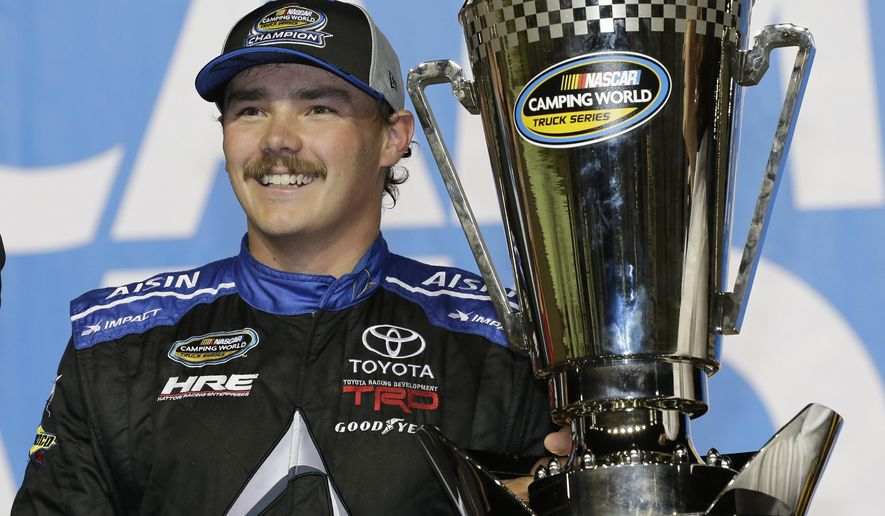 FILE - In this Nov. 16, 2018, file photo, Brett Moffitt stands with his trophy in Victory Lane after winning the NASCAR Truck Series auto racing season championship, at Homestead-Miami Speedway in Homestead, Fla. After winning a NASCAR Truck series title in 2018, Moffitt is still searching for his first win this season. (AP Photo/Terry Renna, File)