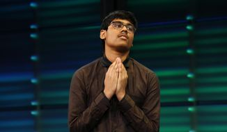 Nihar Janga, 14, of Austin, Texas, reacts with a prayer after winning the National Geographic GeoBee, Wednesday, May 22, 2019, at National Geographic in Washington. Janga is also a past co-winner of the National Spelling Bee, in 2016, when he won in a tie at eleven-years-old. (AP Photo/Jacquelyn Martin)