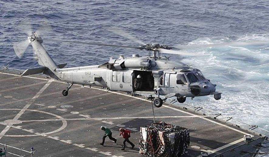 In this Sunday, May 19, 2019, file photo, an MH-60S Sea Hawk helicopter transports cargo from the fast combat support ship USNS Arctic to the Nimitz-class aircraft carrier USS Abraham Lincoln during a replenishment-at-sea operation in the Arabian Sea, as Mideast tensions remain high between Tehran and the United States. (Mass Communication Specialist 3rd Class Darion Chanelle Triplett/U.S. Navy via AP) ** FILE **