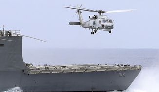 A Taiwan navy S70 helicopter takes off from the stern of a Perry-class frigate during a naval exercise off Hualien County, eastern Taiwan, Wednesday, May 22, 2019. (AP Photo/Chiang Ying-ying)