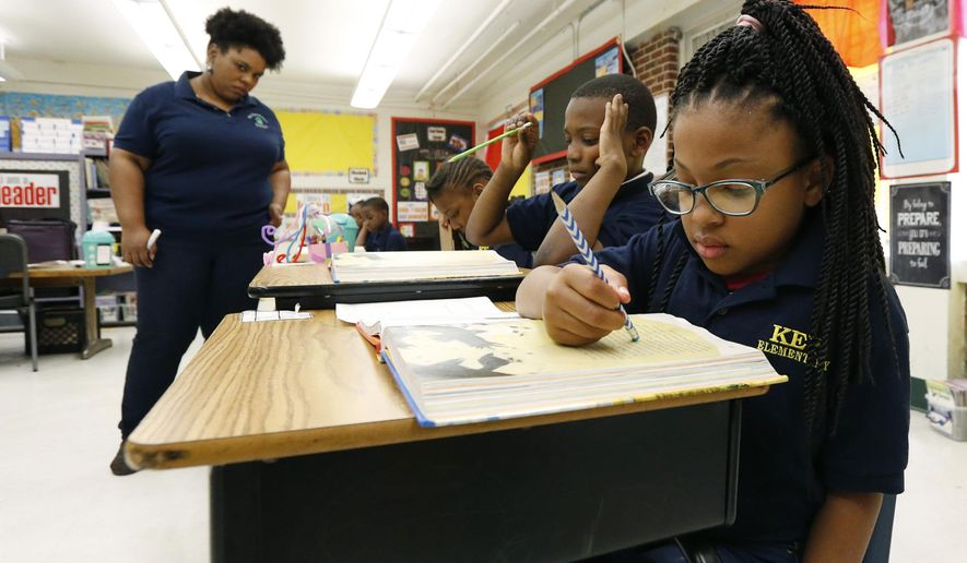 FILE -  In this April 18, 2019 file photograph, Elize'a Scott, a Key Elementary School third grade student, right, reads under the watchful eyes of teacher Crystal McKinnis, left, in Jackson, Miss. About one in four Mississippi third graders failed a toughened reading test on the first try this spring, according to results released Wednesday, May 22, 2019, by the Mississippi Department of Education, leaving it unclear if the students will advance to fourth grade. (AP Photo/Rogelio V. Solis, File)
