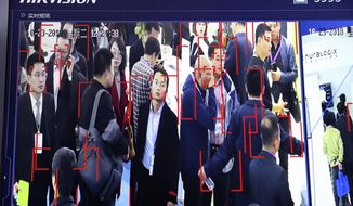 In this photo taken Tuesday, Oct. 23, 2018, visitors are tracked by facial recognition technology from state-owned surveillance equipment manufacturer Hikvision at the Security China 2018 expo in Beijing, China. The Chinese video surveillance company says it is taking concern about the use of its technology seriously following a report that the U.S. may block several Chinese surveillance companies from buying American components. (AP Photo/Ng Han Guan)