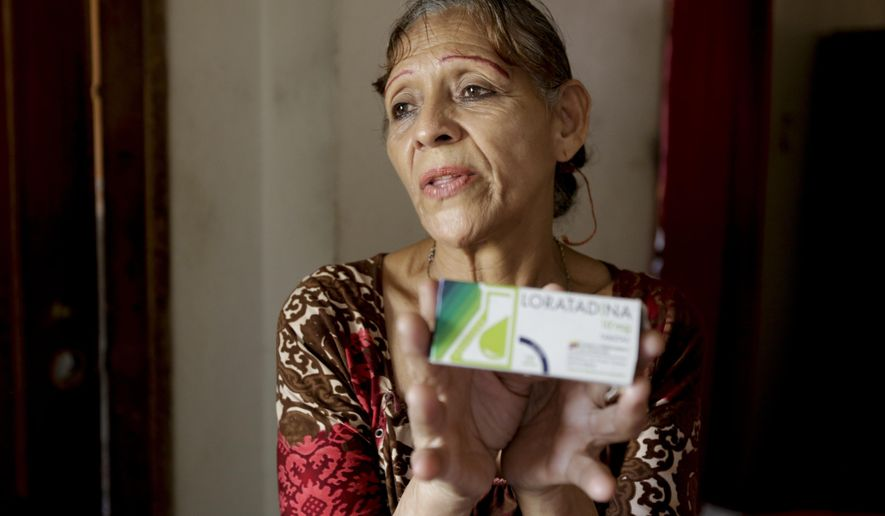 In this April 11, 2019 photo, Bertha Dun shows medicine bought with cryptocurrency through online transfers, in Barquisimeto, Venezuela, Thursday, April 11, 2019. Venezuela's political and economic crisis has now made it a prime testing ground using cryptocurrency to finance social projects or send relief directly to people living in poverty. (AP Photo/Manuel Rueda)