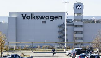 In this Dec. 4, 2015, file photo, a man walks through the employee parking lot at the Volkswagen plant in Chattanooga, Tenn.  (AP Photo/Erik Schelzig, File) **FILE**