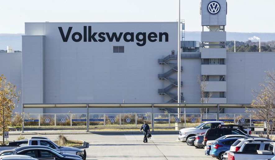 FILE - In this Dec. 4, 2015, file photo, a man walks through the employee parking lot at the Volkswagen plant in Chattanooga, Tenn. In a split decision, the National Labor Relations Board on Wednesday, May 22, 2019,  has ruled in favor of Volkswagen in a setback for unionization efforts at its Chattanooga, Tennessee, plant. The NRLB has dismissed a petition for a union vote by the United Auto Workers based on a technicality. The union intends to refile immediately.  (AP Photo/Erik Schelzig, File)