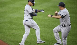 New York Yankees' Gleyber Torres, left, celebrates his home run with third base coach Phil Nevin during the third inning of the team's baseball game against the Baltimore Orioles, Wednesday, May 22, 2019, in Baltimore. (AP Photo/Nick Wass)