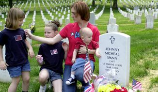 "In this May 27, 2002, file photo Shannon Spann, widow of CIA officer Johnny ""Mike"" Spann, and her three children, from left, Emily, 4, Alison, 10, and Jake, 11 months, visit the grave of their lost husband and father on Memorial Day at Arlington National Cemetery in Arlington, Va. Spann, the first American killed in the Afghan war, was part of a small group of CIA paramilitary officers who went into Afghanistan just 16 days after the al-Qaida attacks of Sept. 11, 2001.  (AP Photo/Mia Aigotti, File)"