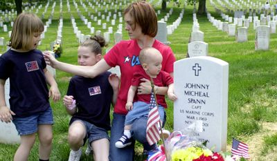 """In this May 27, 2002, file photo Shannon Spann, widow of CIA officer Johnny """"Mike"""" Spann, and her three children, from left, Emily, 4, Alison, 10, and Jake, 11 months, visit the grave of their lost husband and father on Memorial Day at Arlington National Cemetery in Arlington, Va. Spann, the first American killed in the Afghan war, was part of a small group of CIA paramilitary officers who went into Afghanistan just 16 days after the al-Qaida attacks of Sept. 11, 2001.  (AP Photo/Mia Aigotti, File)"""