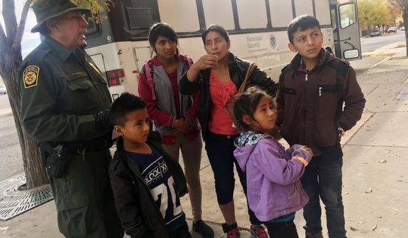In this Thursday, Nov. 29, 2018 photo, a migrant family from Central America waits outside the Annunciation House shelter in El Paso, Texas, after a U.S. Immigration and Customs Enforcement officer drops them off. Volunteer shelters along the U.S.-Mexico border say they are preparing for an expected surged of new immigrants seeking asylum in the U.S. who will need temporary housing as the holidays approach. (AP Photo/Russell Contreras) **FILE**