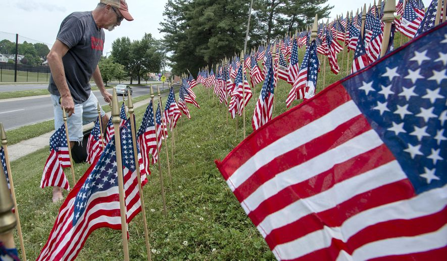 Randy Hartsock places American flags on the embankment outside of American Legion Hackler-Wood Post 145 Thursday, May 23, 2019 in Bristol, Tennessee in preparation for Memorial Day weekend. (AP Photo/David Crigger. Bristol Herald Courier)/Bristol Herald Courier via AP)