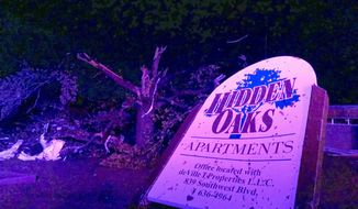 "The sign for the Hidden Oaks apartment complex in Jefferson City Missouri stands bent on May 23, 2019, from an apparent tornado in front of a tree that was ripped apart. A ""violent tornado"" touched down in Jefferson City, Missouri, causing possible fatalities, according to the National Weather Service (AP Photo/David A. Lieb)"