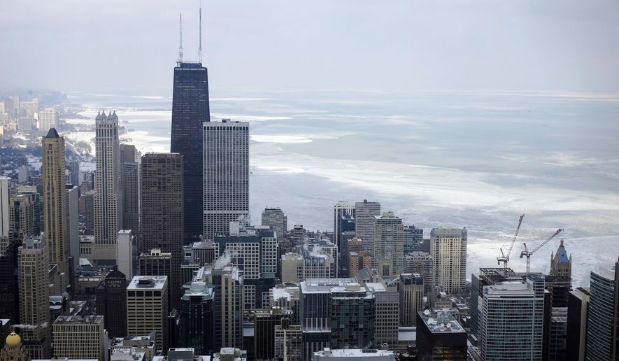 In this Feb. 17, 2015, file photo, ice covered Lake Michigan is seen behind downtown skyline, in Chicago. (AP Photo/Kiichiro Sato, File)