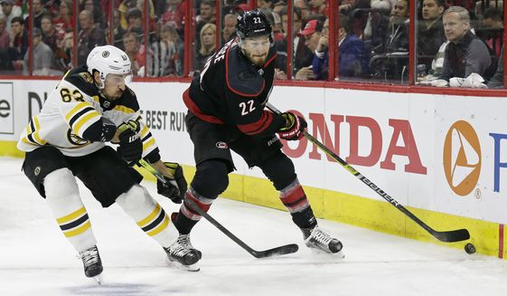 Boston Bruins' Brad Marchand (63) chases the puck with Carolina Hurricanes' Brett Pesce (22) during the first period in Game 4 of the NHL hockey Stanley Cup Eastern Conference final series in Raleigh, N.C., Thursday, May 16, 2019. (AP Photo/Gerry Broome)