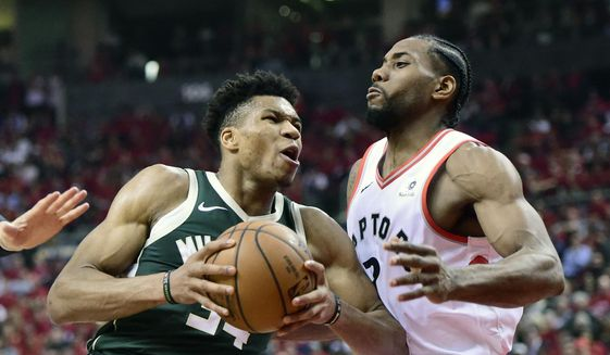 Milwaukee Bucks forward Giannis Antetokounmpo (34) drives to the basket as Toronto Raptors forward Kawhi Leonard (2) defends during the first half of Game 4 of the NBA basketball playoffs Eastern Conference finals, Tuesday, May 21, 2019 in Toronto. (Frank Gunn/The Canadian Press via AP) **FILE**