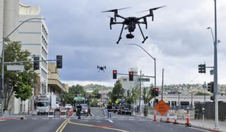 In this May 21, 2019 photo, two drones fly above Lake Street in downtown Reno, Nev., on, as part of a NASA simulation to test emerging technology that someday will be used to manage travel of hundreds of thousands of commercial, unmanned aerial vehicles (UAVs) delivering packages. It marked the first time such tests have been conducted in an urban setting. (AP Photo/Scott Sonner)