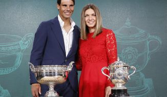 Defending champions Spain's Rafael Nadal, left, and Romania's Simona Halep pose next to the cups during the draw of the French Open tennis tournament at the Roland Garros stadium in Paris, Thursday, May 23, 2019. The French Open tennis tournament starts Sunday May 26. (AP Photo/Michel Euler)