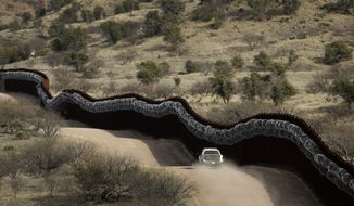 This March 2, 2019, file photo shows a Customs and Border Control agent patrols on the U.S. side of a razor-wire-covered border wall along the Mexico east of Nogales, Ariz. (AP Photo/Charlie Riedel) ** FILE **