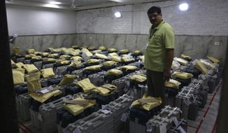 An election official checks electronic voting machines as counting votes of India's massive general elections begins in New Delhi, India, Thursday, May 23, 2019. The count is expected to conclude by the evening, with strong trends visible by midday. (AP Photo/Manish Swarup)