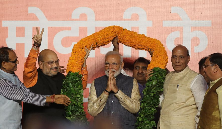Bharatiya Janata Party (BJP) President Amit Shah, second left, and Home Minister Rajnath Singh, second right, present a giant floral garland to Indian Prime Minister Narendra Modi at the party headquarters in New Delhi, India, Thursday, May 23, 2019. Indian Prime Minister Narendra Modi's party claimed it had won reelection with a commanding lead in Thursday's vote count, while the stock market soared in anticipation of another five-year term for the pro-business Hindu nationalist leader. (AP Photo/Manish Swarup)
