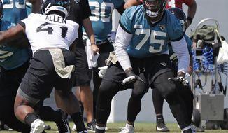 Jacksonville Jaguars offensive lineman Jawaan Taylor (75) looks to block Jacksonville Jaguars defensive end Josh Allen (41) during an NFL football practice, Tuesday, May 21, 2019, in Jacksonville, Fla. (AP Photo/John Raoux)