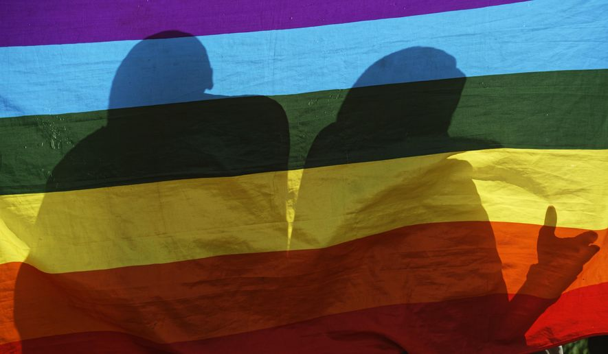 In this photo taken Friday, May 17, 2019, LGBT refugees living in Kenya stand behind a rainbow flag as they protest against their treatment by authorities, outside an office of the UN refugee agency UNHCR in Nairobi, Kenya. Kenya's High Court is due to rule Friday, May 24, 2019 on whether laws that criminalize same sex relations are unconstitutional. (AP Photo/Ben Curtis)