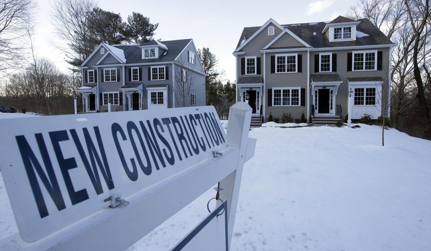 FILE- In this Feb. 21, 2019, file photo a newly constructed homes sit near a sign in Natick, Mass. On Thursday, May 23, the Commerce Department reports on sales of new homes in April. (AP Photo/Steven Senne, File)